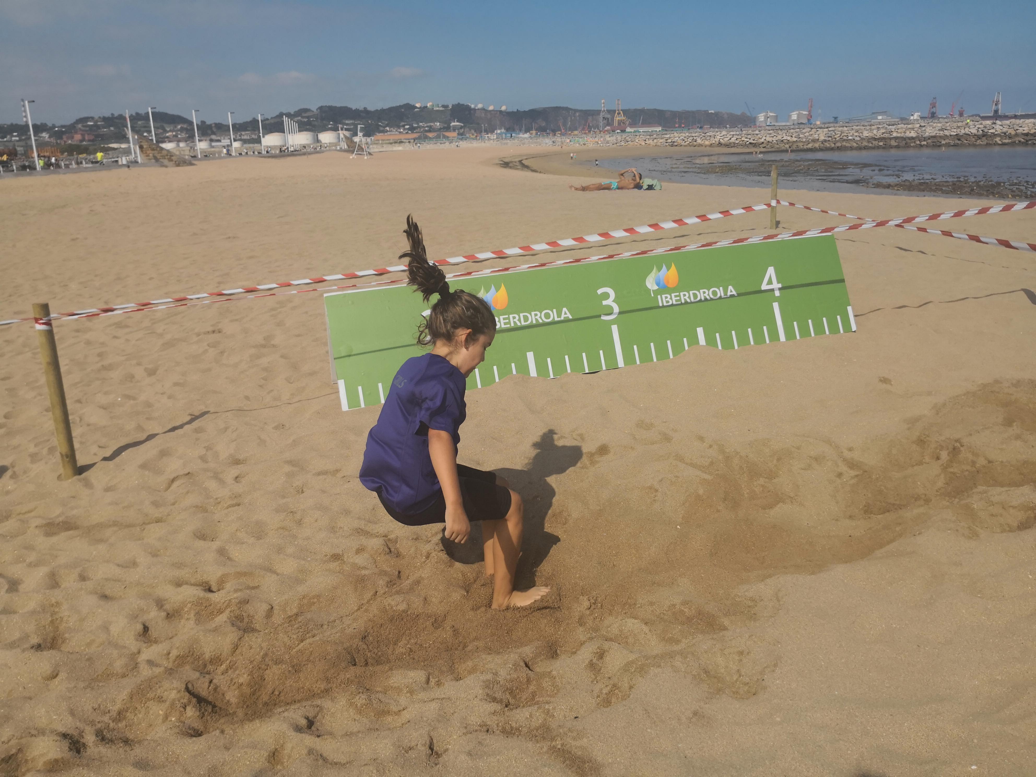 Tour Iberdrola en Gijón – niña realizando salto de longitud en la arena de la playa
